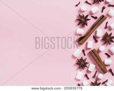 Marshmallows and winter spices on pink background with copyspace. Flat lay or top view. Background of colorful mini marshmallows, cinnamon, cloves and star anise. Winter food background concept.