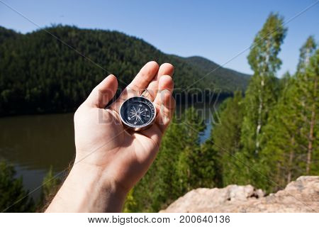 Hand holding the compass. Hike concept. Travel concept.