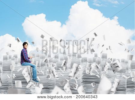 Young man in casual clothing sitting on pile of documents among flying papers with cloudly skyscape on background. Mixed media.