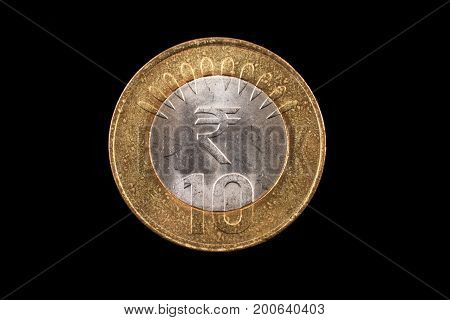 An extreme close up of an Indian ten rupee coin on a solid black background