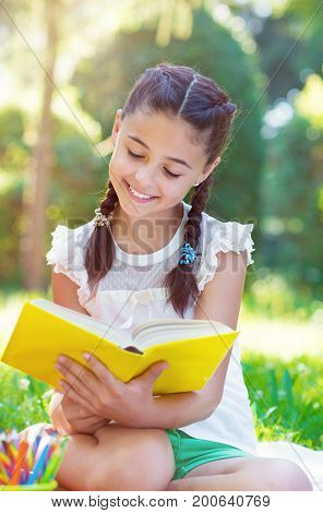 Portrait Of Pretty Young Girl Reading Book In Park