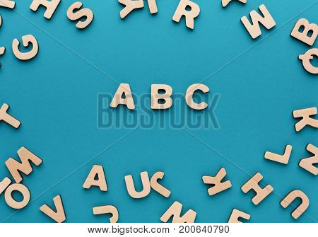 Back to school concept. Alphabet ABC made of wooden letters on blue background