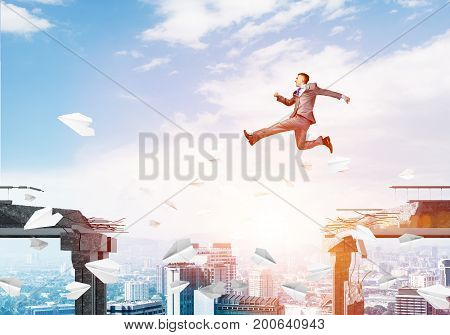 Businessman jumping over gap with flying paper planes in concrete bridge as symbol of overcoming challenges. Cityscape with sunlight on background. 3D rendering.