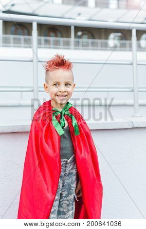 Happy little child playing superhero. Kid having fun outdoors. Kid superhero in a red cloak.A little boy with red hair. Child in uniform.