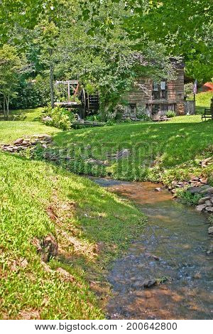 a small stream flows from an old gristmill
