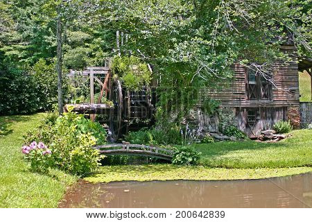 an old gristmill in front of a muddy pond