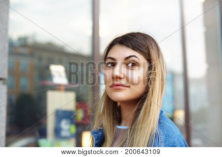Pretty girl relaxing outdoors. Attractive young blonde woman of Euroepan appearance shopping alone in city center having pleased happy look standing outside modern building going to enter shop