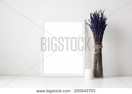 Beautiful cozy shot of white table in living room or home office desk with glass vase or bottle with dried lavender flowers candle and empty picture frame with copy space for your photograph