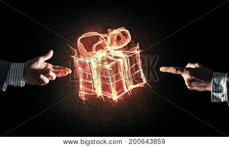 Glowing fire gift box icon in palm on dark background