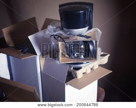 Stack opened cardboard boxes with brand new electric coffee maker on a top filterd photo