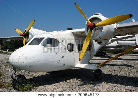 Old abandoned propeller plane, white plane with yellow propellers