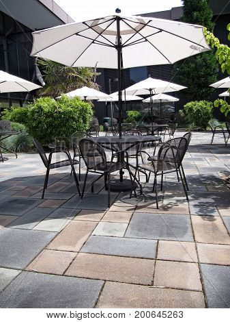 Patio with black metal tables and chairs and white umbrellas.