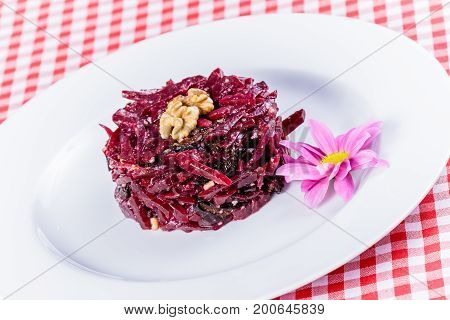 Salad with boiled beet, walnut and prunes