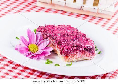 Russian layered herring and vegetable salad on white plate