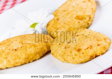 Chicken cutlets with flower on white plate