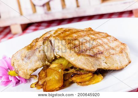 Pork loin with fried potato and onion on white plate
