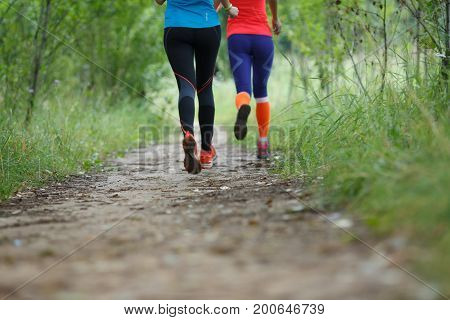 Image from bottom of two running sportswomen in forest