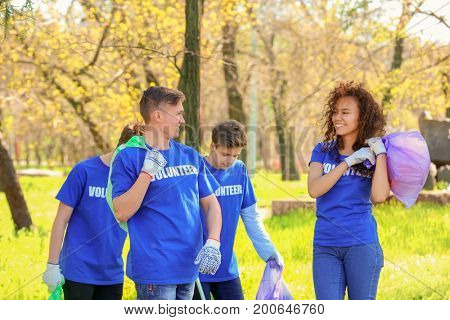 Group of young volunteers in park on sunny day