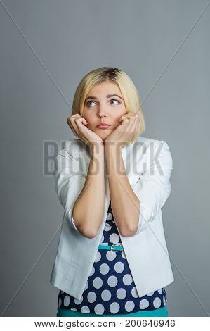 Pensive girl on empty gray background in studio