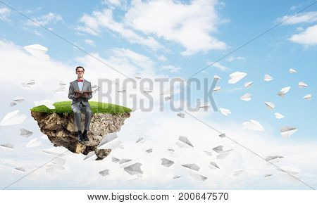 Funny man in red glasses and suit sitting on green island and reading book