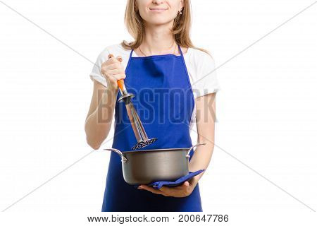 Young woman in apron with a saucepan and masher on white background isolation