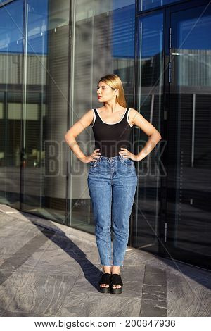 People urban style street fashion and modern lifestyle concept. Attractive fashionable young female model with blonde hair wearing trendy sleeveless top jeans and sandals posing on street