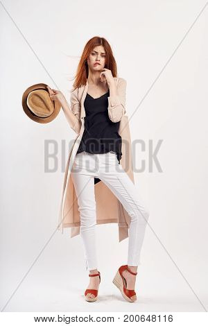 Beautiful young woman on a light background holds a hat in full growth, fashion, beauty, style.