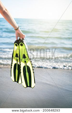 Woman´s hand keep snorkel and swimming fins on a sandy beach. Water sports. Snorkeling. Travel and holiday concept