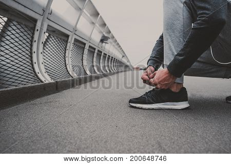 Young man preparing to run in the city, tying jogging shoes.