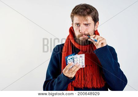 A man with a beard on a light background holds a thermometer in his mouth, flu, sickness, sick, empty space for copying.