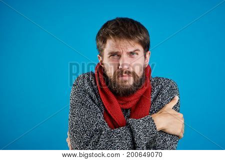 Man with a beard on a blue background ties up a scarf, sweater, flu, sickness, sick, empty space for copying.