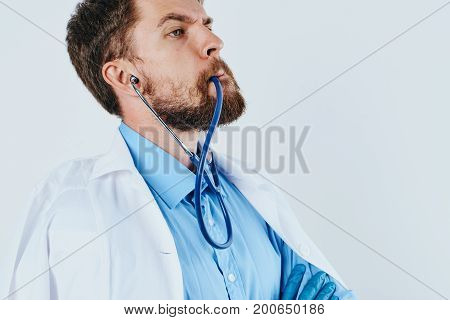 Man with a beard against a light background, stethoscope, medical clothes, doctor, medicine.