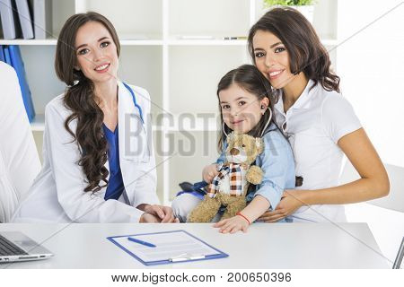 Happy mother and child with teddy bear and stethoscope at pediatrician office