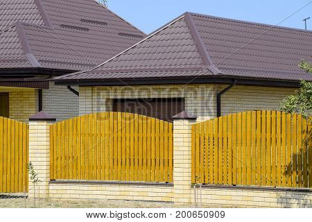 Brick House With Corrugated Metal Profile Roof And Wooden Fence. Beautiful View Of The Facade. Style