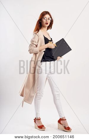 Beautiful woman on white isolated background holds documents in hat and glasses full-length.
