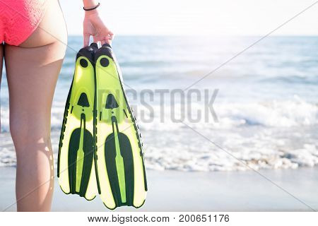Sexy young woman buttocks with swimming fins on a sandy beach. Water sports. Holiday and travel concept.
