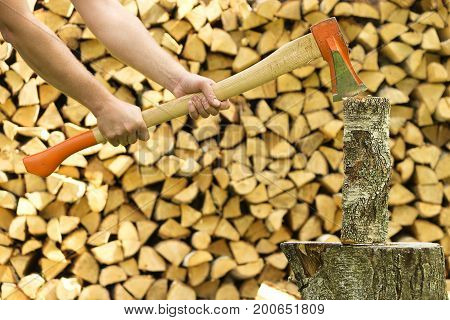 Man hands chopping firewood with axe. Lumberjack cuts the firewoods.