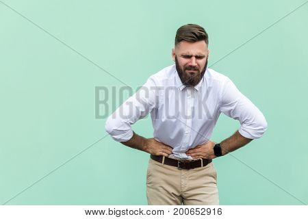 Bad emotions and feelings pain. Young man experiencing stomach pain isolated on light green background. Indoor studio shot