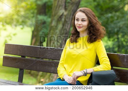Portrait of the beautiful fashionable girl in yellow pullover on bench in park