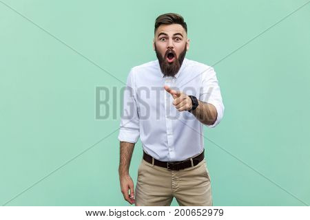 Wow that's great! Portrait of young adult with beard with shocked facial expression. Indoor studio shot