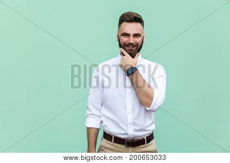 Stylish bearded man with appealing dark eyes smiling into camera. Businessman with beard grinning having cheerful look. Holding hand on chin. Positive emotions. Indoor studio shot