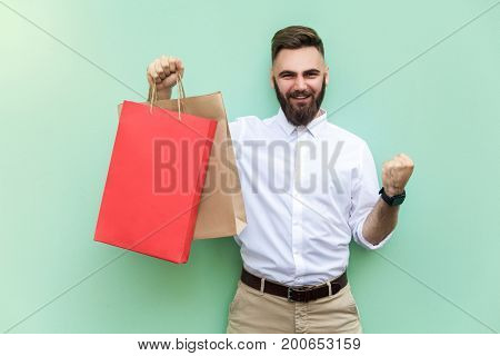 Shopping Young adult successful businessman looking at camera and toothy smile. Indoor studio shot.