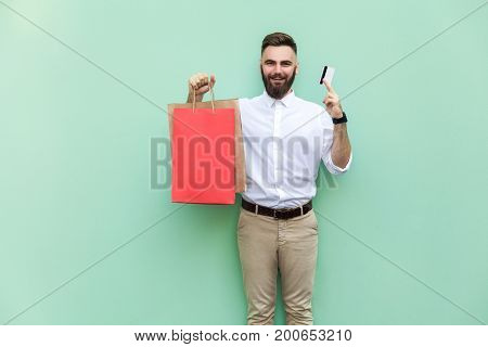 Businessman using credit card for online shopping. Looking at camera and toothy smile. Indoor studio shot green background