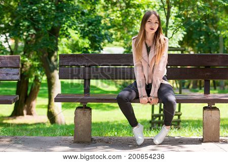 Portrait of beautiful informal fashionable girl on bench in park