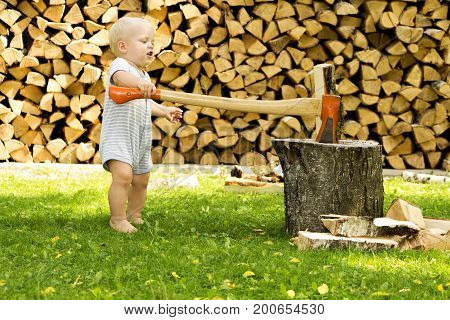 Funny toddler cutting firewoods with a huge axe.