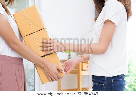 Young asian girl together freelancer business private working at home office holding packaging sort box delivery online market on purchase orders to customer.