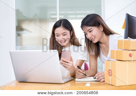 Young asian girl together teamwork freelancer business private working at home office with laptop note mobile packaging delivery online market on purchase checking orders to customer.