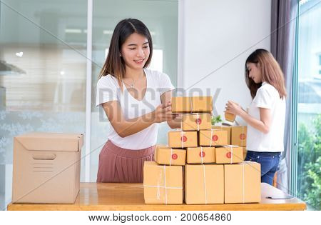 Young asian girl together freelancer business private working at home office with laptop note coffee packaging sort box delivery online market on purchase orders to customer.