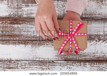 Woman holding presents gift box with red ribbon laid on wooden table background