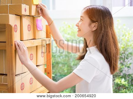 Young asian girl freelancer working at home office with notes on packaging boxes for delivery online market on purchase orders to customer.